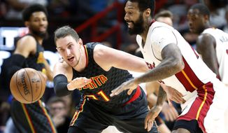 Atlanta Hawks forward Mike Muscala passes the ball as Miami Heat forward James Johnson, right, defends during the first half of an NBA basketball game, Wednesday, Feb. 1, 2017, in Miami. (AP Photo/Wilfredo Lee)