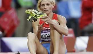 FILE - In this Aug. 4, 2012 file photo Russia's Antonina Krivoshapka takes off her shoes following a women's 400-meter semifinal during the athletics in the Olympic Stadium at the 2012 Summer Olympics, London. The IOC said Wednesday, Feb. 1, 2017 it has stripped Russia of an Olympic silver medal from the women's 4x400-meter relay at the 2012 London Games for doping. The IOC says Antonina Krivoshapka tested positive for the anabolic steroid turinabol in reanalysis of samples from the 2008 and 2012 Olympics. (AP Photo/Kirsty Wigglesworth, file)