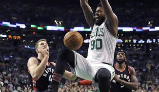 Boston Celtics forward Amir Johnson (90) dunks over Toronto Raptors center Jakob Poeltl, left, after driving past forward DeMarre Carroll, right, during the second quarter of an NBA basketball game in Boston, Wednesday, Feb. 1, 2017. (AP Photo/Charles Krupa)