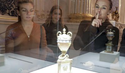 Tennis players Martina Hingis, right, and Simona Halep, left, look at exhibits during their visit to the Faberge Museum in St.Petersburg, Russia, Tuesday, Jan. 31, 2017.   The tennis players are here for the St. Petersburg Ladies Trophy-2017 tennis tournament which will end Sunday, Feb. 5. (AP Photo/Dmitri Lovetsky)