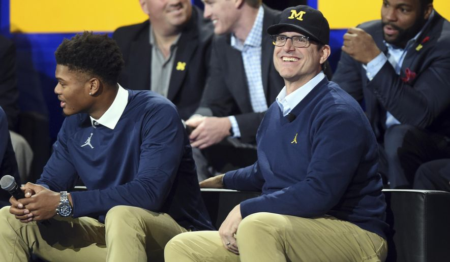 """Michigan head football coach Jim Harbaugh smiles as he sits on stage during the """"Signing of the Stars"""" event on national signing day at Crisler Center in Ann Arbor, Mich., Wednesday, Feb. 1, 2017. (Melanie Maxwell/The Ann Arbor News via AP)"""