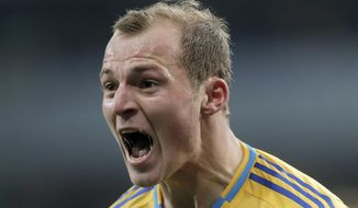 FILE - In this Nov. 15, 2013 file photo, Ukraine's Roman Zozulya celebrates after scoring during the first leg 2014 World Cup qualifying soccer match against France at the Olympiyskiy national stadium in Kiev, Ukraine. The transfer of Ukraine striker Roman Zozulya from Real Betis to second-division club Rayo Vallecano Wednesday Feb. 1, 2017 is being called off in Spain after protests from fans who accused the player of having connections to radical groups back home. (AP Photo/Efrem Lukatsky, File)