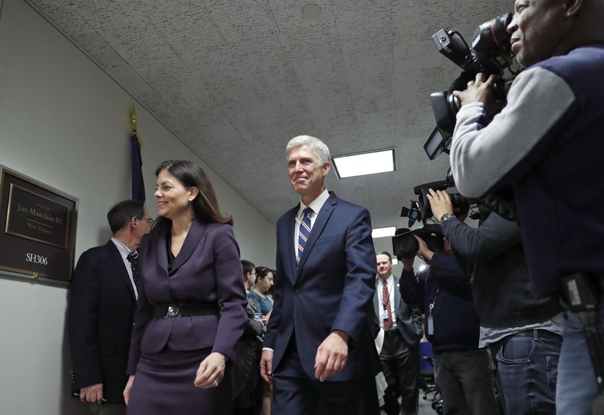 Supreme Court Justice nominee Neil Gorsuch, center arrives for a meeting with Sen. Joe Manchin, D-W.Va., on Capitol Hill, Wednesday, Feb. 1, 2017 in Washington. Former Sen. Kelly Ayotte from New Hampshire walks with Gorsuch at left. (AP Photo/Alex Brandon)