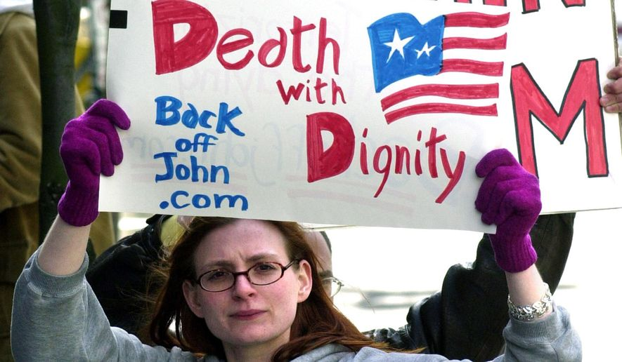 At midnight on Feb. 18, 2017, Washington, D.C. became the 7th jurisdiction in the U.S. to allow physician-assisted suicide. In this March 22, 2002, file photo, Stacey Richter holds a sign outside a federal courthouse in Portland, Ore., as a hearing begins to decide the fate of Oregon's physician-assisted suicide law.  (AP Photo/Don Ryan, File)