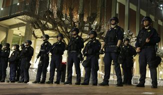 University of California at Berkeley police guard the building where Breitbart News editor Milo Yiannopoulos was to speak Wednesday, Feb. 1, 2017, in Berkeley, Calif. A small group of people with their faces covered broke windows, hurled fireworks at police officers and threw smoke bombs, prompting UC Berkeley officials to cancel Yiannopoulos's talk Wednesday evening. (AP Photo/Ben Margot)