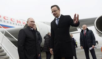 Russian President Vladimir Putin, left, is greeted by Hungarian Minister of Foreign Affairs and Trade Peter Szijjarto at the to Liszt Ferenc International Airport in Budapest, Hungary, Thursday, Feb.  2, 2017. (Tamas Kovacs/MTI via AP)