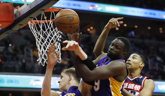 Los Angeles Lakers forward Luol Deng (9) and teammate Timofey Mozgov (20), of Russia, box out Washington Wizards forward Otto Porter Jr. (22) during the first half of an NBA basketball game in Washington, Thursday, Feb. 2, 2017. (AP Photo/Manuel Balce Ceneta)