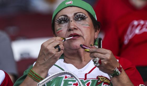 A Mexican baseball fan touches up her lipstick while watching a Caribbean Series game between Cuba's Granma and the Dominican Republic's Licey Tigers, in Culiacan, Mexico, Wednesday, Feb. 1, 2017. Culiacan's Tomateros Stadium is host to the 2017 Series featuring Puerto Rico, Dominican Republic, Cuba and Mexico from Feb. 1 through Feb. 7. (AP Photo/Luis Gutierrez)