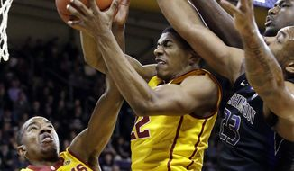 Southern California's Shaqquan Aaron (0) and De'Anthony Melton (22) reach for a rebound along with Washington's Carlos Johnson (23) during the first half of an NCAA college basketball game Wednesday, Feb. 1, 2017, in Seattle. (AP Photo/Elaine Thompson)