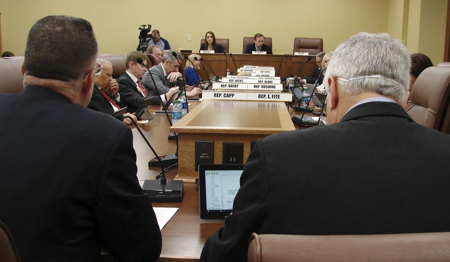 Col. Paul Deckert, left front, of New Orleans, from the Center for Security Policy, and Rep. Brandt Smith testify before the Arkansas House Judiciary Committee on Thursday, Feb. 2, 2017, in Little Rock, Ark., about a bill that would require state judges to use American-based law when deciding cases. The bill passed on a voice vote despite concerns it could infringe on the judiciary branch and was sent to the full House. (AP Photo/Kelly P. Kissel)