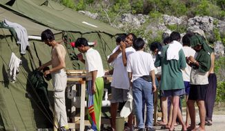 "FILE - In this Sept. 21, 2001, file photo, men shave, brush their teeth and prepare for the day at a refugee camp on the Island of Nauru. Australia's Prime Minister Malcolm Turnbull insisted Thursday, Feb. 2, 2017, that a deal struck with the Obama administration that would allow mostly Muslim refugees rejected by Australia to be resettled in the United States was still on, despite President Donald Trump dubbing the agreement ""dumb"" and vowing to review it. (AP Photo/Rick Rycroft, File)"