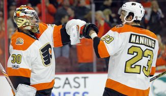 Philadelphia Flyers' Michal Neuvirth, left, and Brandon Manning tap gloves at the end of the team's NHL hockey game against the Montreal Canadiens, Thursday, Feb. 2, 2017, in Philadelphia. (AP Photo/Tom Mihalek)