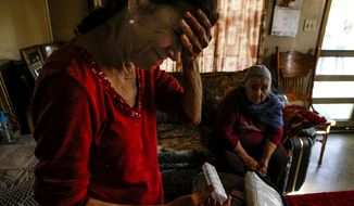 ADVANCE FOR SUNDAY, FEB. 5, 2017 - In this Friday, Dec. 16, 2016 photo, Nina Newell, left, a home health worker, looks through medication for her mother, Maria Mata, right, at her mother's home in Brownsville, Texas. Along Texas' southern border, home health care accounts for more than one in ten total jobs, making the Rio Grande Valley the nation's capital of home health care. ( Michael Ciaglo /Houston Chronicle via AP)