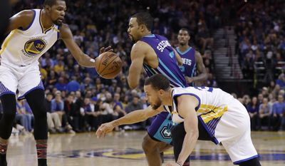 Charlotte Hornets' Ramon Sessions, center, is defended by Golden State Warriors' Stephen Curry, right, and Kevin Durant during the first half of an NBA basketball game Wednesday, Feb. 1, 2017, in Oakland, Calif. (AP Photo/Marcio Jose Sanchez)