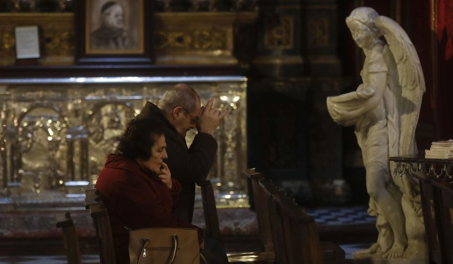 Faithful pray in St. John Cathedral in downtown Valletta, Malta, Thursday, Feb. 2, 2017. After a quarter-century as Malta's governing party, the conservative Nationalist Party scrambled to line up a transgender young man as a candidate for next year's Parliamentary elections in hopes of reversing a stinging, landslide 2013 loss to its socialist archrivals who came to power with an agenda heavy on LGBT rights.  (AP Photo/Gregorio Borgia)