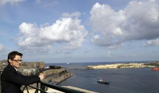 Alex Mangion looks out towards the harbor during an interview with the Associated Press, in Valletta, Wednesday, Feb. 1, 2017. Lithe and dapper in a navy-blue suit as he gazed at this capital city's storied Grand Harbor, Alex Mangion proudly described becoming Malta's first transgender politician, winning a local office on the conservative Nationalists' ticket in a country that until just a few years ago had been a last bastion in Western Europe of social norms largely dictated by the Catholic church.  (AP Photo/Gregorio Borgia)