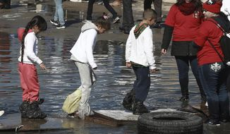 Children with plastic bags covering their shoes walk across the U.S. - Mexico border on the Rio Grande to meet with relatives, in Ciudad Juarez, Mexico, Saturday, Jan 28, 2017. Hundreds of people from Ciudad Juarez gathered along the U.S.-Mexico border to reunite with relatives from El Paso, Texas, for a few precious minutes. (AP Photo/Christian Torres)