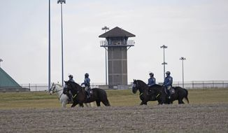 """Mounted police patrol travel along Smyrna Landing Road alongside James T. Vaugh Corrections center, Thursday, Feb. 2, 2017 in Smyrna, Del.   Inmates used """"sharp instruments"""" to assume control of the building at the James T. Vaughn Correction Center on Wednesday, taking three prison guards and a woman counselor hostage.  (Suchat Pederson/The Wilmington News-Journal via AP)"""