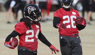 FILE - In this Wednesday, Jan. 18, 2017, file photo,  Atlanta Falcons running backs Devonta Freeman, left, and Tevin Coleman run drills during practice for the NFL football NFC championship game in Flowery Branch, Ga. Freeman and Coleman feel like brothers. They're going to enjoy it while they can, because this is not likely to be a long-term partnership. (Curtis Compton/Atlanta Journal-Constitution via AP, File)