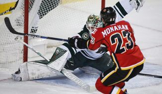 Minnesota Wild goalie Devan Dubnyk gives up a goal to Calgary Flames center Sean Monahan (23) during the first period of an NHL hockey game Wednesday, Feb. 1, 2017, in Calgary, Alberta. (Jeff McIntosh/The Canadian Press via AP)
