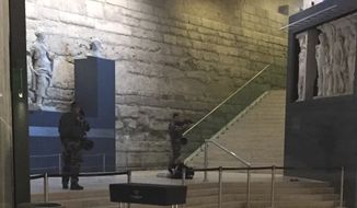 "The body of a man lays on the floor as two soldiers guard him in the Louvre museum, Friday, Feb. 3, 2017 in Paris. A knife-wielding man shouting ""Allahu akbar"" attacked French soldiers on patrol near the Louvre Museum Friday in what officials described as a suspected terror attack. The soldiers first tried to fight off the attacker and then opened fire, shooting him five times. (AP Photo)"