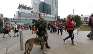 Kiley Hayden and K-9 Bbrooke, with the Los Angeles County Sheriff's Department, keep watch outside the George R. Brown Convention Center, site of the media center and NFL Experience for the NFL Super Bowl 51 football game Friday, Feb. 3, 2017, in Houston. (AP Photo/David J. Phillip)
