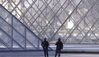 Police officers patrol at the pyramid outside the Louvre museum in Paris,Friday, Feb. 3, 2017. Paris police say a soldier has opened fire outside the Louvre Museum after he was attacked by someone, and the area is being evacuated. (AP Photo/Thibault Camus)