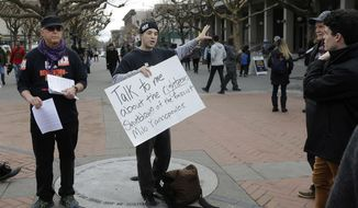 Protesters hold signs while talking to students and others on the University of California, Berkeley, campus in Berkeley, Calif., Thursday, Feb. 2, 2017. Chaos that erupted at the University of California, Berkeley, to oppose right-wing provocateur Milo Yiannopoulos was shocking not just for the images of protesters setting fires, smashing windows and hurling explosives at police, but because of where it took place. (AP Photo/Jeff Chiu)