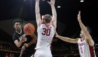 Colorado guard Dominique Collier passes next to Stanford center Grant Verhoeven (30) and guard Christian Sanders (1) during the first half of an NCAA college basketball game Thursday, Feb. 2, 2017, in Stanford, Calif. (AP Photo/Marcio Jose Sanchez)