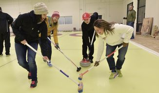 Curling instructor Jon Anderson, 17, center right in red baseball cap, gives sweeping instruction to, from left, Jennifer Born, Kristi Portugue and Sharon Zell at Dakota Curling in Lakeville, Minn., on Tuesday, Jan. 24, 2017.  Dakota Curling, a nonprofit organization, signed a 20-year lease for the new space in Holyoke Plaza where Total Hockey Minnesota had been running its training programs. (John Autey/Pioneer Press via AP)
