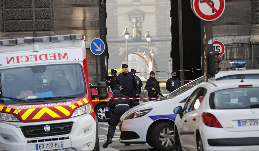 Police officers cordon off the area outside the Louvre museum near where a soldier opened fire after he was attacked in Paris, Friday, Feb. 3, 2017. Police say the soldier opened fire outside the Louvre Museum after he was attacked by someone, and the area is being evacuated. (AP Photo/Christophe Ena)