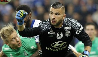 FILE - In this file photo dated Sunday, Oct. 2, 2016, Lyon's goalkeeper Anthony Lopes, right, bats the ball away during the French League One soccer match between Lyon and Saint-Etienne, in Decines, near Lyon, central France. Lopes is considered to have defamed the name of bitter rivals Saint-Etienne during a recent match, making him a marked man for upcoming match between Lyon and Saint-Etienne. (AP Photo/Laurent Cipriani, FILE)