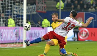 Hamburg's Mergim Mavraj, right, and Leverkusen's goalkeeper Bernd Leno battle for the ball during the Bundesliga soccer match between Hamburger SV and Bayer Leverkusen at the Volksparkstadion in Hamburg, Germany, Friday Feb. 3, 2017. (Axel Heimken/dpa via AP)
