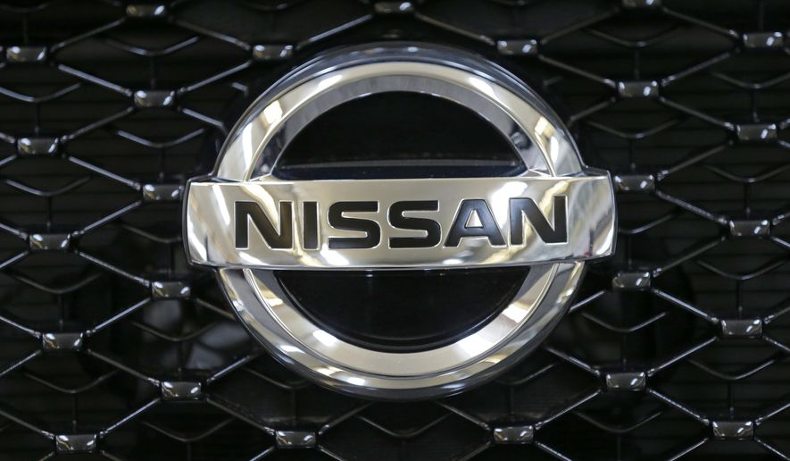 FILE - This Feb. 14, 2013 file photo shows the Nissan logo on the grill of a 2013 Nissan Pathfinder on display at the 2013 Pittsburgh Auto Show in Pittsburgh.  The company is recalling more than 341,000 of the midsize cars in the U.S. because the doors might open if a rear window is lowered.The recall covers Altimas from the 2015 through 2017 model years. (AP Photo/Gene J. Puskar, File)