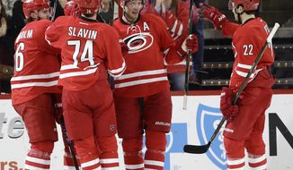 Carolina Hurricanes' Jordan Staal (11) is congratulated by Brett Pesce (22), Jaccob Slavin (74) and Elias Lindholm (16), of Sweden, following Staal's goal against the Edmonton Oilers during the first period of an NHL hockey game in Raleigh, N.C., Friday, Feb. 3, 2017. (AP Photo/Gerry Broome)