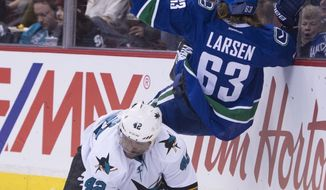 Vancouver Canucks defenseman Philip Larsen (63) goes into the boards with San Jose Sharks right wing Joel Ward (42) during first-period NHL hockey game action in Vancouver, British Columbia, Thursday, Feb. 2, 2017. (Jonathan Hayward/The Canadian Press via AP)