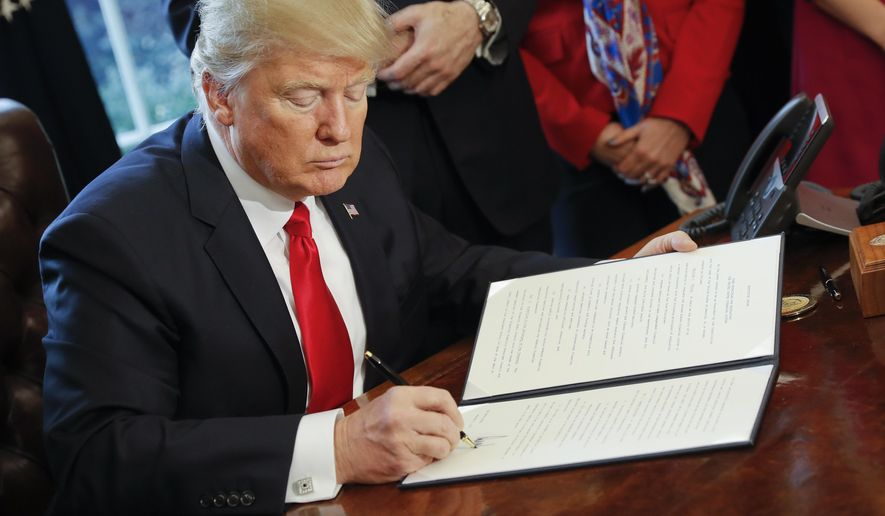 President Donald Trump signs an executive order in the Oval Office of the White House in Washington, in this Friday, Feb. 3, 2017, file photo. Trump signed an executive order that directed the Treasury secretary to review the 2010 Dodd-Frank financial oversight law, which reshaped financial regulation after 2008-2009 crisis. (AP Photo/Pablo Martinez Monsivais) ** FILE **