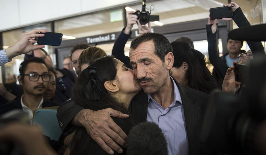 """Marjan K. Vayghan, left, gives a kiss to her uncle Ali Vayeghan as he arrives at the international terminal at Los Angeles International Airport in Los Angeles on Thursday, Feb. 2, 2017. Vayeghan, who had been turned away from the airport under President Donald Trump's executive order barring immigrants from seven Muslim-majority nations, returned Thursday to an emotional welcome from family members who greeted him with California-grown flowers and well-wishers who sang """"This Land Is Your Land."""" (Ed Crisostomo/The Orange County Register via AP)"""