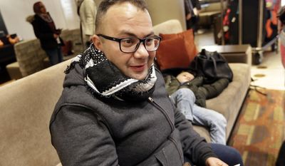 Munther Alaskry sits in the lobby of his New York hotel as his son Hassan naps behind him on a couch, Friday, Feb. 3, 2017. Alaskry and his family arrived at New York's Kennedy Airport after the Trump administration reversed course and said he and other interpreters who supported the U.S. military could come to America. They spent nearly a week in limbo in Baghdad, thinking their hopes of starting a new life free from death threats had been shattered.(AP Photo/Richard Drew)