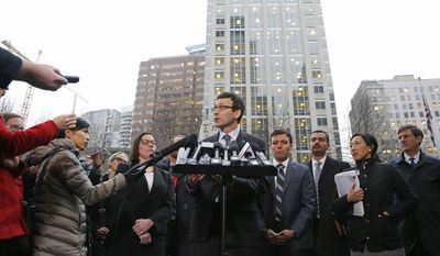 Washington Attorney General Bob Ferguson, center, talks to reporters Friday, Feb. 3, 2017, following a hearing in federal court in Seattle. A U.S. judge on Friday temporarily blocked President Donald Trump's ban on people from seven predominantly Muslim countries from entering the United States after Washington state and Minnesota urged a nationwide hold on the executive order that has launched legal battles across the country.(AP Photo/Ted S. Warren)
