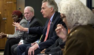 Virginia Gov. Terry McAuliffe, center, gestures as he speaks to a group at the ADAMS Islamic center in Sterling, Va., Friday, Feb. 3, 2017. (AP Photo/Steve Helber)