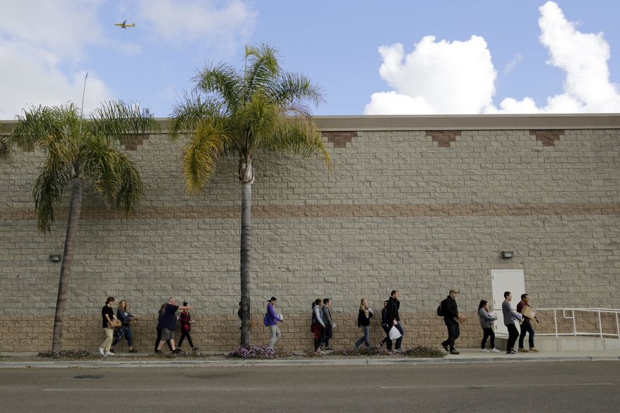 """Volunteers carry donated items towards a group of undocumented migrants looking for work as day laborers alongside a hardware store Saturday, Feb. 4, 2017, in San Diego. President Donald Trump's promised crackdown on """"sanctuary cities"""" has revealed the deep divide on immigration in liberal and conservative states, with some moving to follow his order and others breaking with the U.S. government to protect immigrants in the country illegally. (AP Photo/Gregory Bull)"""