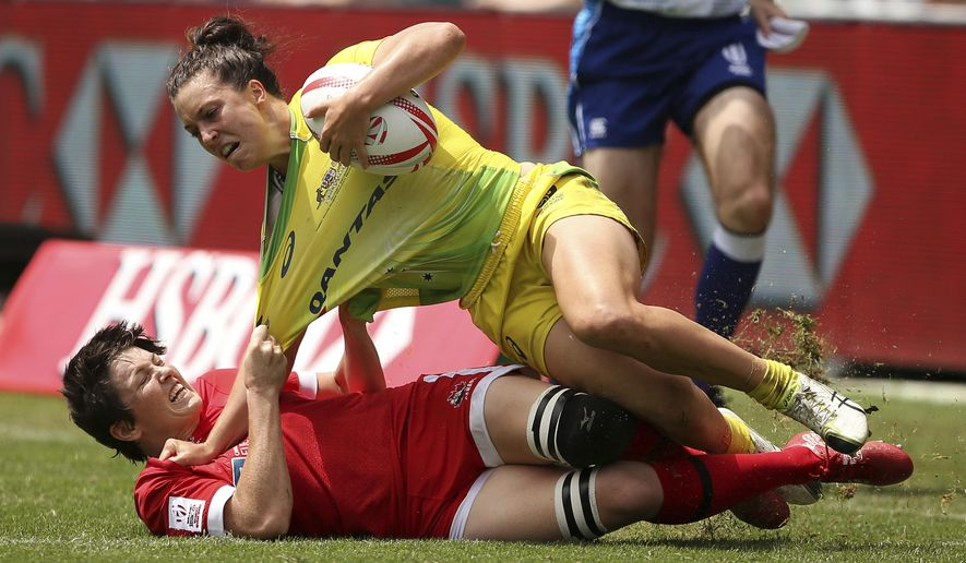 Canada's Brittany Benn, bottom, brings down Australia's Emilee Cherry during their women's semifinal match at the World Rugby Sevens Series tournament in Sydney, Saturday, Feb. 4, 2017. (AP Photo/Rick Rycroft)