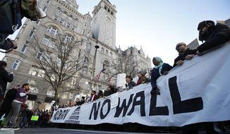 Protesters march along Pennsylvania Avenue past the Trump International Hotel during a rally protesting the immigration policies of President Donald Trump, near the White House in Washington, Saturday, Feb. 4, 2017. (AP Photo/Manuel Balce Ceneta)