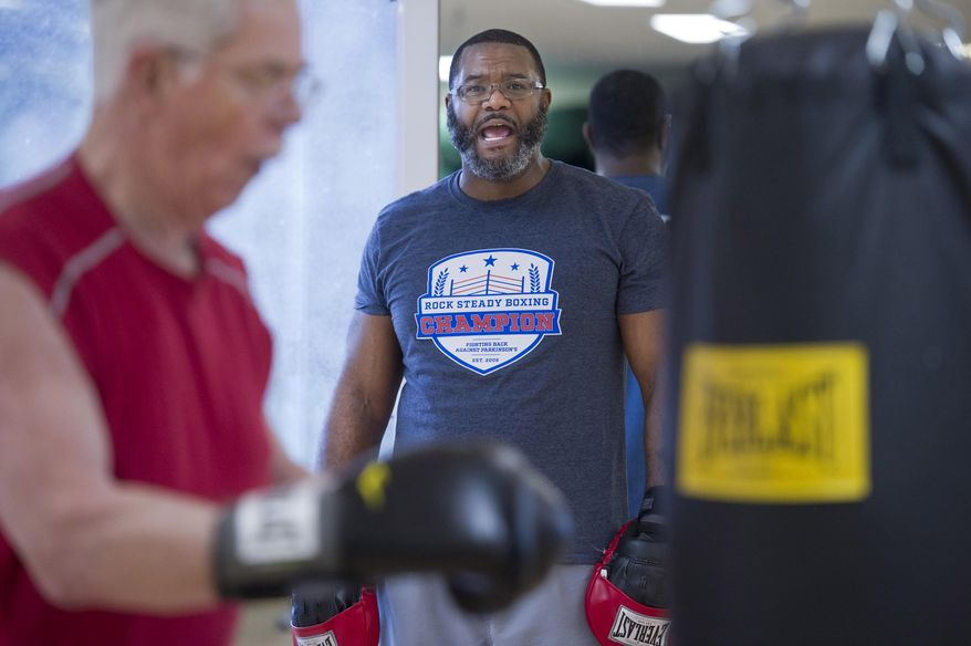ADVANCE FOR WEEKEND FEB. 4-5, 2017 AND THEREAFTER - In this photo taken Jan. 26, 2017, physical trainer Kirk Burke yells encouragement to Ozzie Osborn as he works the heavy bag during the Rock Steady Boxing class at Pavitt Health & Fitness in Juneau, Alaska. The class is offered to those with various stages of Parkinson's disease. (Michael Penn/Juneau Empire via AP)
