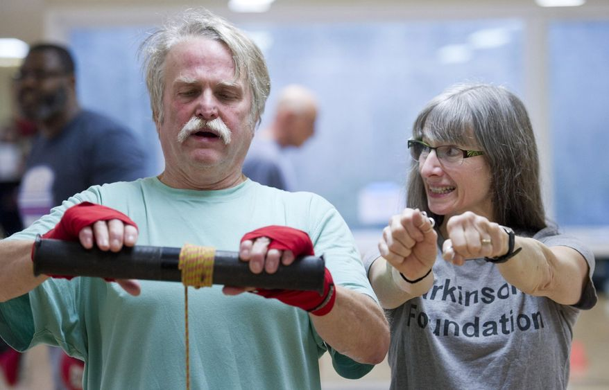ADVANCE FOR WEEKEND FEB. 4-5, 2017 AND THEREAFTER -- In this photo taken Jan. 26, 2017, Luann McVey gives her husband, Richard Steele, encouragement as he participates in the Rock Steady Boxing class at Pavitt Health & Fitness in Juneau, Alaska. The class is offered to those with various stages of Parkinson's disease. (Michael Penn/Juneau Empire via AP)