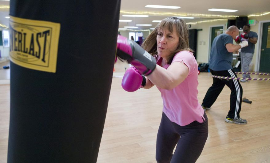 ADVANCE FOR WEEKEND FEB. 4-5, 2017 AND THEREAFTER -- In this photo taken Jan. 26, 2017, Kerry Howard works out on the heavy bag during the Rock Steady Boxing class at Pavitt Health & Fitness in Juneau, Alaska. The class is offered to those with various stages of Parkinson's disease. (Michael Penn/Juneau Empire via AP)