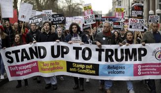 People hold a banner as they take part in a protest march in London, against U.S. President Donald Trump's ban on travellers and immigrants from seven predominantly Muslim countries entering the U.S., Saturday, Feb. 4, 2017. Thousands of protesters have marched on Parliament in London to demand that the British government withdraw its invitation to U.S. President Donald Trump. (AP Photo/Matt Dunham) ** FILE **