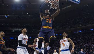 Cleveland Cavaliers' LeBron James (23) dunks next to New York Knicks' Carmelo Anthony (7) and Courtney Lee (5) during the first half of an NBA basketball game, Saturday, Feb. 4, 2017, in New York. (AP Photo/Andres Kudacki)