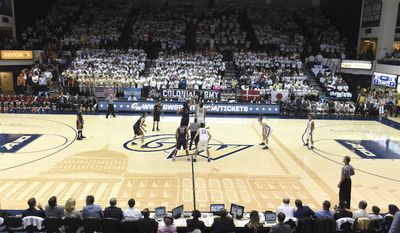 In this Nov. 16, 2015 photo provided by The George Washington University, George Washington plays Virginia in front of a sold out crowd at an NCAA college basketball game at the Charles E. Smith Center in Washington, DC. College basketball floors once had simple designs, the only flair usually the addition of color in the lane or at midcourt. Court designs have taken a creative twist over the past few years with schools adding elaborate detail. (The George Washington University via AP)